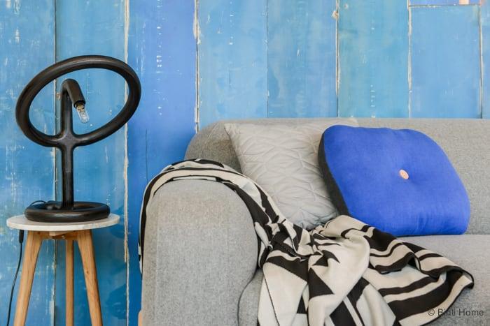 Woonkamer inrichten met een grijze bank en kobaltblauw en grafisch zwart ©BintiHome
