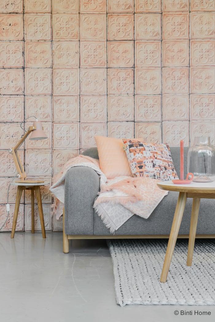 Woonkamer styling met zacht roze pastellen en een grijze bank ©BintiHome