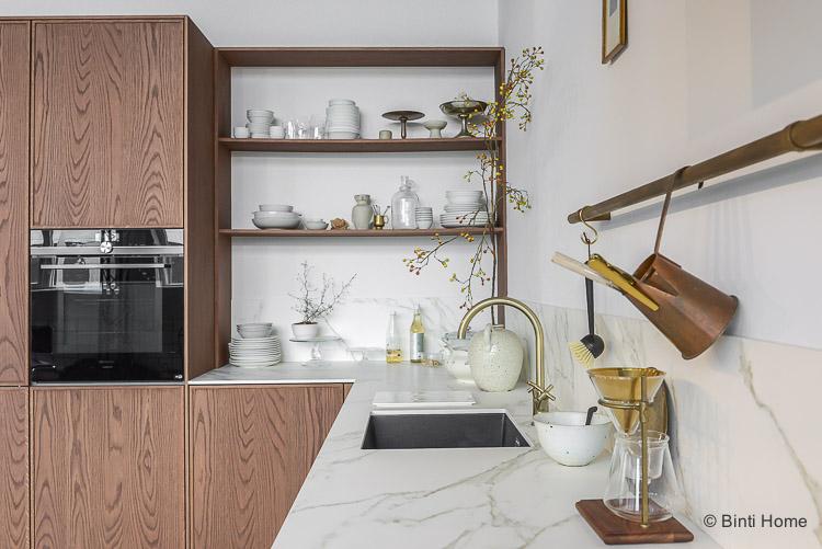 Vtwonen keuken in donker eiken met een gouden kraan en marmer look
